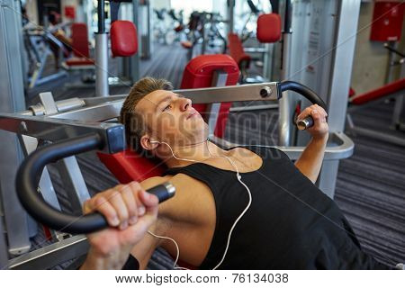 sport, equipment, technology, lifestyle and people concept - young man with earphones flexing chest muscles on gym machine