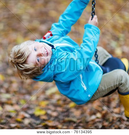 Little Kid Boy Having Fun On Autumn Playground