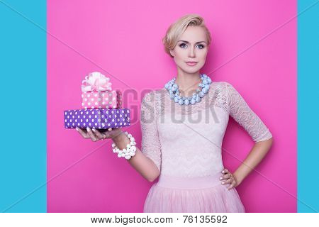 Beautiful young woman with cream colored dress holding pink and purple gift boxes