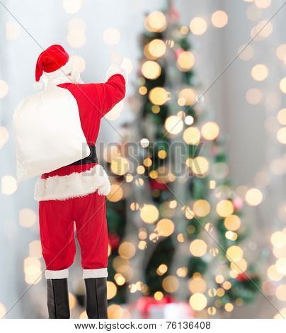 christmas, holidays and people concept - man in costume of santa claus with bag pointing finger from back over yellow lights background over tree lights background