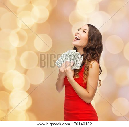 christmas, holidays, sale, banking and people concept - smiling woman in red dress with us dollar money over beige lights background