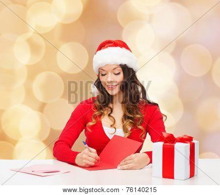 christmas, holidays, celebration, greeting and people concept - smiling woman in santa helper hat with gift box writing letter or sending post card over beige lights background