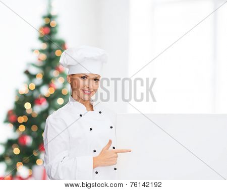 cooking, advertisement, holidays and people concept - smiling female chef, cook or baker pointing finger to white blank board over living room and christmas tree background