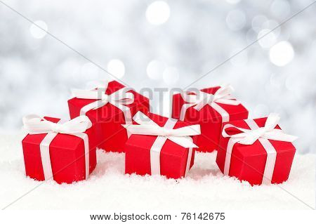 Red gift boxes in snow with twinkling lights