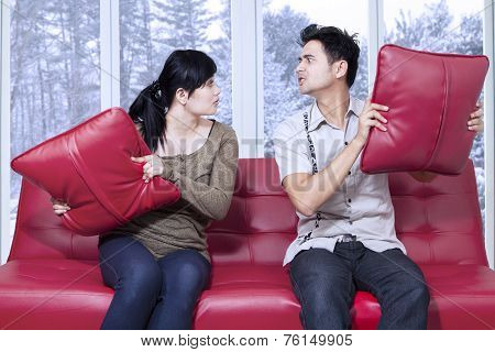 Angry Couple Throwing Pillow To Each Other