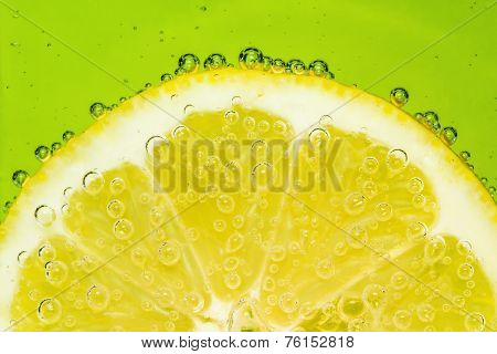 Fresh lemon in soda water covered with bubbles