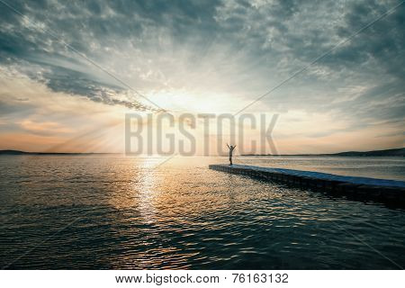 Woman With Arms Raised Standing On Pier At Sunset