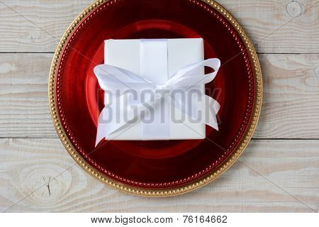 High angle shot of a present wrapped in white paper and tied with white ribbon and bow. The present is centered on a red charger on top of a gold charger. Horizontal format on white wood table.
