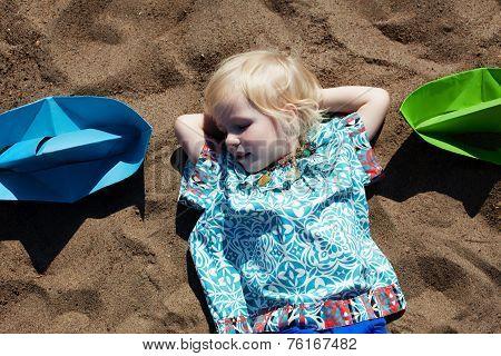 Cute little girl fell asleep on sand