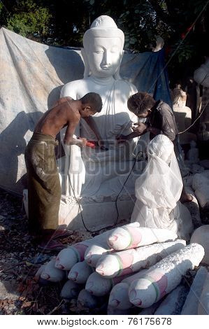 Burmese Man Carving A Large Marble Buddha Statue.