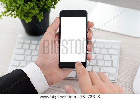 Businessman Sitting At Desk And Holding Phone With Isolated Screen
