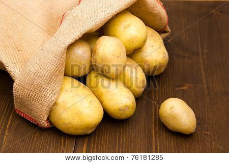 Sack of potatoes on wood