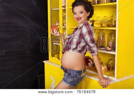 Beautiful Brunette Woman On A 7Th Month Pregnancy In Plaid Shirt And Jeans Shorts On A Yellow Kitche