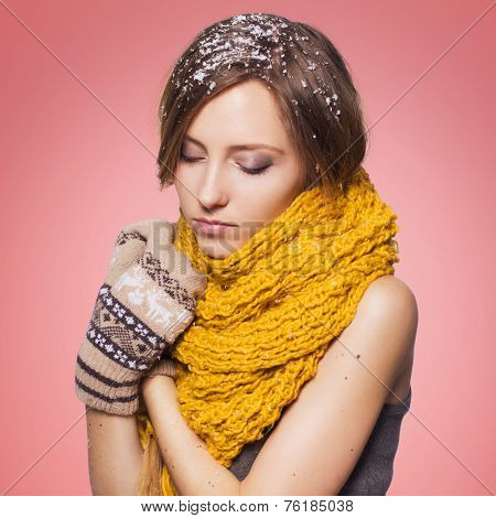 Beautiful redhair woman in winter outfit: warm sweater scarf and hat with snow all over her. Isolate