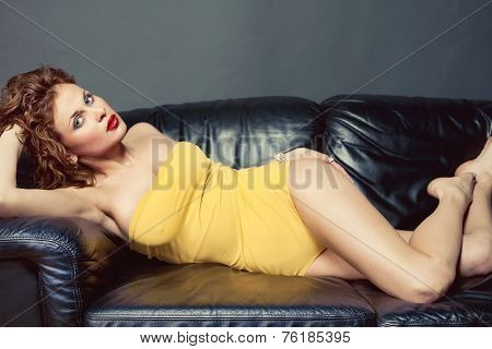 Sensual Red-haired Woman Posing On A Sofa In Yellow Lingerie