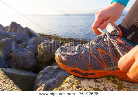 Woman Tying The Shoe Laces On Her Running Shoes