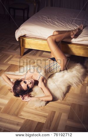 Brunette woman with curly hairstyle laying on a floor near luxury bed