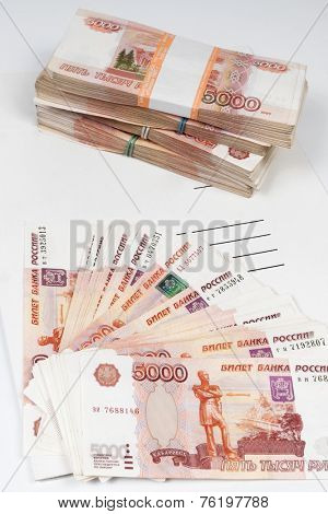 packs of ruble notes piled and a fan from notes on the white folder