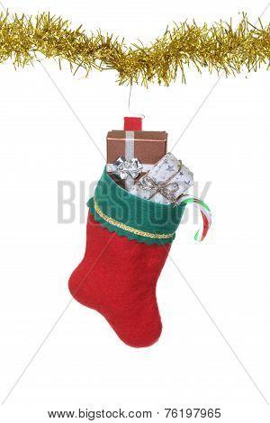 filled christmas stocking hanging on gold garland