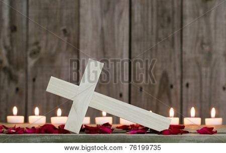 Fallen wooden cross by burning candles and rose petals with rustic wood background