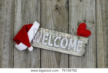 Welcome sign with Christmas Santa Claus hat hanging on rustic wooden background