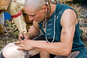 stock photo of american indian  - Native American male creating a tattoo on arm the old - JPG