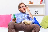 image of mimicry  - Man eating popcorn on the sofa  - JPG