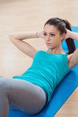 foto of flat stomach  - Attractive woman doing abs workout at gym for muscle toning and flat stomach - JPG