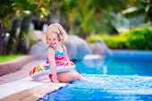 foto of swimming pool family  - Adorable little girl with curly hair wearing a colorful swimming suit playing with water splashes at beautiful pool in a tropical resort having fun during family summer vacation - JPG