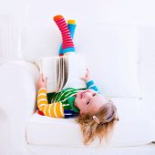 stock photo of couch  - Happy laughing little girl reading a book relaxing on a white couch at home - JPG