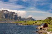 image of fjord  - Scenic fjord on Lofoten islands with typical fishing hut and towering mountain peaks - JPG