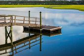 picture of inlet  - On a calm morning a boat dock reflects in the blue waters of an inlet along the Atlantic Coast - JPG