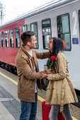 stock photo of long distance relationship  - pair on arrival on a platform at a station - JPG