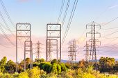 foto of transmission lines  - High voltage electrical  transmission power lines against late afternoon sky - JPG