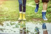 picture of wet feet  - Young couple in colorful wellies walking in muddy nature - JPG