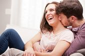 image of arousal  - love understanding are what this couple shows off while lying on their living room sofa embracing and enjoying