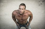 stock photo of shirtless  - Shirtless muscular man shot from above looking at camera standing outdoor - JPG