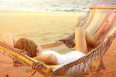 foto of sunny beach  - Woman in a white dress lying in a hammock on a sunny beach next to the ocean in Belize - JPG