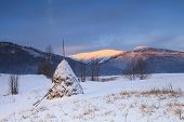 stock photo of haystacks  - Snowy haystack on the background of the Carpathian Mountains and Valleys - JPG