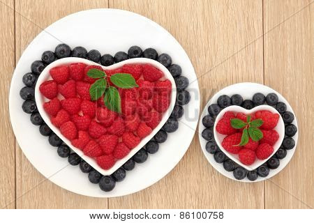 Blueberry and strawberry antioxidant fruit in heart and round shaped dishes over oak wood background.