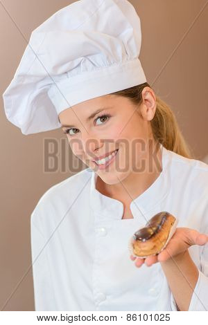 Female baker presenting you with an eclair
