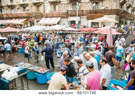 CATANIA, ITALY- SEP 17,2014: Sellers and byers on the famous fish market in Catania on Sep 17, 2014, Italy. This market is also tourist attraction in Catania, Sicily.