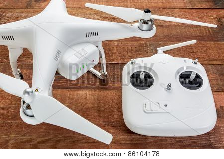 Fort Collins, CO, USA - March 17, 2015:  DJI Phantom 2 quadcopter drone with a radio controller against rustic wooden wood table