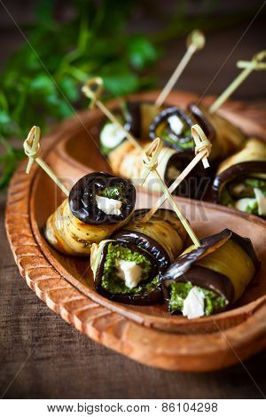 Eggplant rolls with pesto and feta on vintage wooden plate. Soft focus