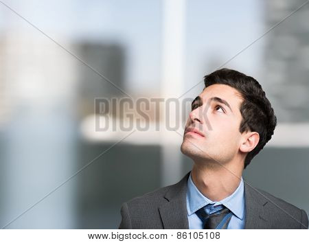 Portrait of a young businessman looking up in his office