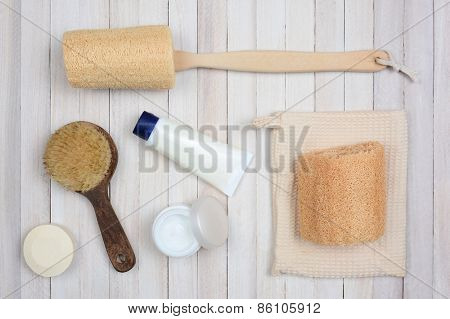 Bath and Spa accessories on a white rustic wood surface. Items include: luffa, brush, creams and soap. Overhead view in horizontal format.