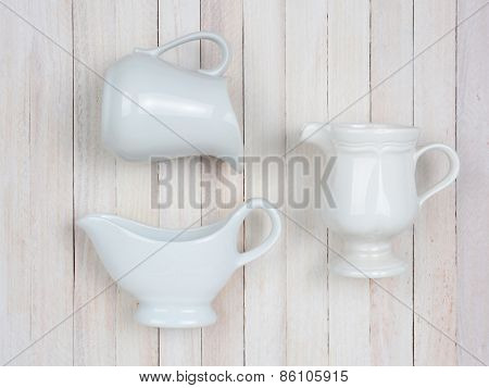 Closeup of three white ceramic pitchers on a rustic whitewashed wood table. High angle shot in horizontal format.