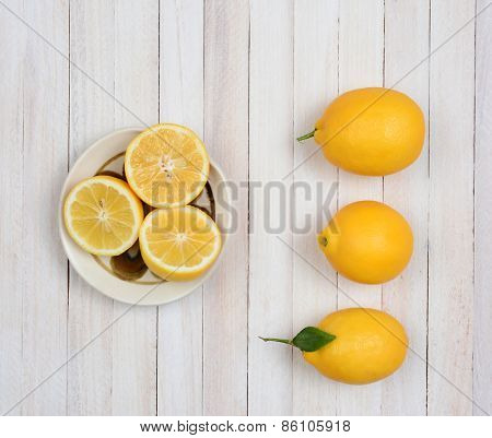 High angle still life of three whole lemons and three lemon halves in a bowl on a rustic white wood kitchen table.