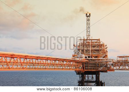 Offshore oil and rig platform in sunset or sunrise time. Construction of production process in the s