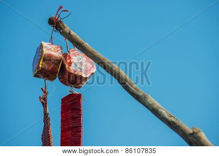 The red chinese fire crackers for celebration day hanging on branch.